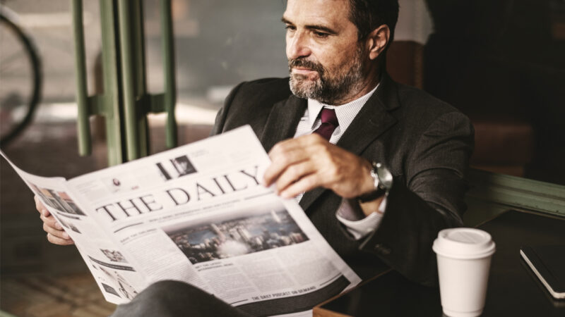 Politician reading news on sofa